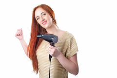 Redhead woman with long hair holding hair dryer Stock Images