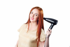 Redhead woman with long hair holding hair dryer Stock Photography
