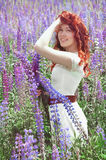 Redhead woman with long hair in lupine field Stock Images