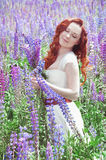 Redhead woman with long hair in lupine field Stock Photography