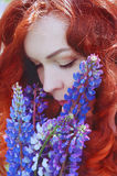 Redhead woman with long hair in lupine field Stock Photo