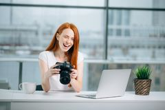 Redhead woman looking at camera while working on laptop. Young redhead woman looking at camera while working on laptop. Photographer with her camera and laptop Royalty Free Stock Image
