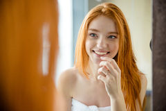 Redhead woman looking at her reflection in mirror Stock Photo