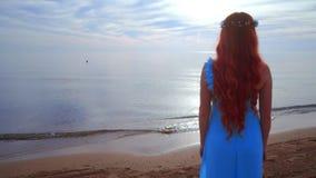 Redhead woman looking at sea. Rear view woman beach. Woman on sea beach stock footage