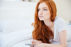 Redhead woman lying on the bed with smartphone Stock Images