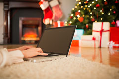 Redhead woman lying on floor using laptop at christmas Royalty Free Stock Photos