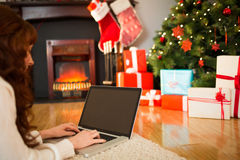 Redhead woman lying on floor using laptop at christmas Royalty Free Stock Images