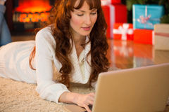 Redhead woman lying on floor using laptop at christmas Stock Image
