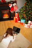 Redhead woman lying on floor using laptop at christmas Royalty Free Stock Photography