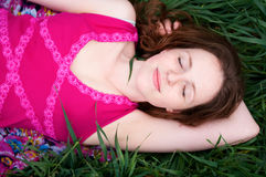 Redhead woman lying on the green Stock Images