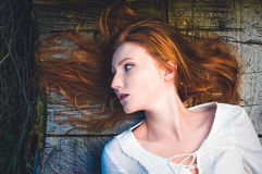 Redhead woman lying on a tree trunk Royalty Free Stock Photography