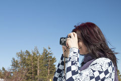 Redhead woman with an old camera. In winter against blue sky Stock Image