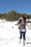 Redhead woman with an old camera. In winter against blue sky Royalty Free Stock Photography