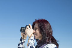 Redhead woman with an old camera. In winter against blue sky Royalty Free Stock Photo