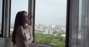 Redhead woman opens window and enjoys fresh air in her day off. stock video
