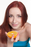 A redhead woman with an orange. A beautiful redhead woman holding a half of orange isolated on white Royalty Free Stock Image