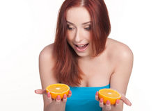A redhead woman with an orange. A beautiful redhead woman holding a half of orange isolated on white Royalty Free Stock Photography