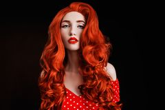 Redhead woman with pale skin and red lips on black background. Girl with copper hair in retro dress. Red curly wig. Redhead woman royalty free stock photo