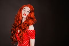 Redhead woman with pale skin and red lips on black background. Girl with copper hair in retro dress. Red curly wig. Redhead woman royalty free stock image