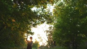 Redhead woman in pants and white shirt posing - sunset country off road with beautiful evening sun light rays, green. Sunset country off road with beautiful stock video