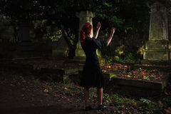 Redhead woman performing ritual at grave Stock Photography