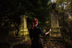 Redhead woman performing ritual at grave Stock Photos