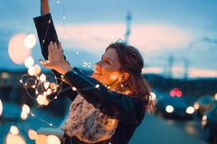 Redhead woman playing with fairy lights outdoors and smile at evening, teal and orange style. Happy young redhead woman playing with fairy lights outdoors and stock photo