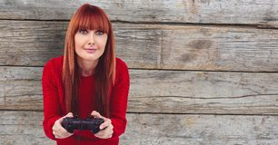 Redhead woman playing video game against wall. Digital composite of Redhead woman playing video game against wall Royalty Free Stock Photography