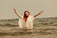 Redhead woman playing in water during summertime stock images