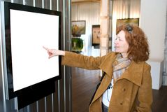 Redhead woman points to a picture Stock Photography