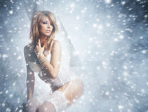A redhead woman posing in white lingerie on the snow Royalty Free Stock Photography