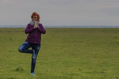 Redhead woman practicing yoga tree position stock photography