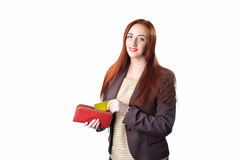 Redhead woman pulling credit card out of a red purse Royalty Free Stock Photo