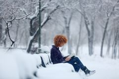 Redhead woman reading a book in the snow. Woman sitting on a bench full of snow reading a book stock photos