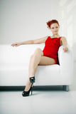 Redhead woman in a red dress on white couch. Luxurious redhead woman in a red dress on white couch stock photography