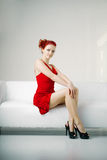 Redhead woman in a red dress on white couch Royalty Free Stock Photo