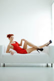 Redhead woman in a red dress on white couch Stock Photos