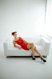 Redhead woman in a red dress on white couch Royalty Free Stock Photos