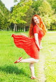 Redhead woman with red fluttering dress Stock Photos