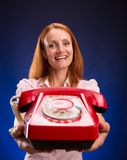 Redhead woman with red telephone Royalty Free Stock Images