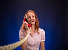 Redhead woman with red telephone Stock Image