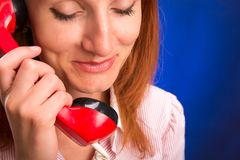 Redhead woman with red telephone Stock Photo