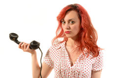 Redhead woman with a retro look speaking at a vintage phone Stock Photo