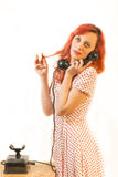 Redhead woman with a retro look speaking at a vintage phone Royalty Free Stock Photo