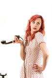 Redhead woman with a retro look speaking at a vintage phone Stock Image