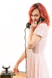 Redhead woman with a retro look speaking at a vintage phone Stock Images
