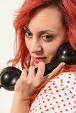 Redhead woman with a retro look speaking at a vintage phone Stock Photos
