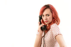 Redhead woman with a retro look speaking at a vintage phone Royalty Free Stock Photos