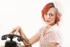 Redhead woman with a retro look waiting for the phone Stock Photography