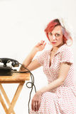 Redhead woman with a retro look waiting for the phone Royalty Free Stock Photography